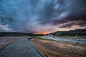 Evening Storm Clouds Gather Over A Boardwalk In Biscuit Basin, Yellowstone National Park by Bryan Jolley