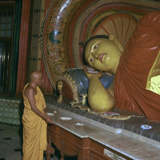 Buddhist priest before the image of a reclining Buddha. Artist: Unknown-Unknown-Photographic Print