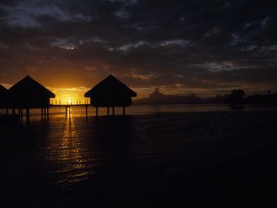 Bungalows over the Water at Sunset at an Exclusive Hotel on Tahiti-Paul Sutherland-Photographic Print