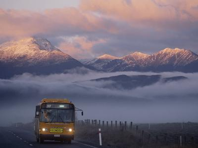 Bus at Sunrise with the Mountains Covered in a Blanket of Fog-Annie Griffiths-Photographic Print