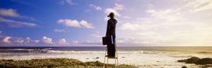 Businessman Standing on a Ladder and Looking Through Binoculars, California, USA