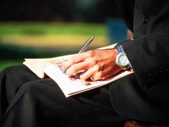 Businessman Writing on Newspaper-Stephen Umahtete-Photographic Print