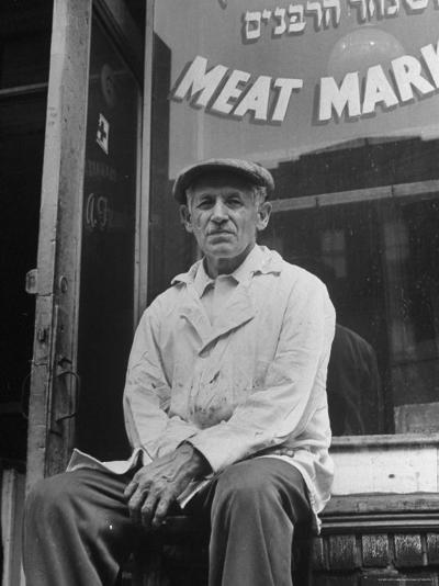 Butcher Taking a Break, Sitting in Front of Meat Market-Ed Clark-Photographic Print