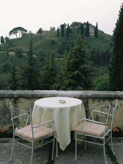 Cafe Table and Chairs Overlooking a Villa on a Hill-Todd Gipstein-Photographic Print