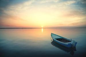 Canoe Floating on the Calm Water under Amazing Sunset