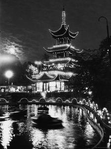 Chinese Styled Tower Viewed from Across an Ornamental Lake at Night in the Tivoli Amusement Park by Carl Mydans