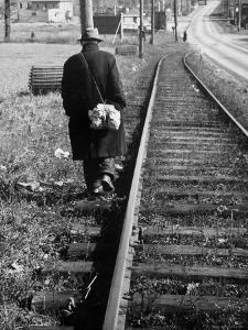 Elderly Hobo, with Bundle Strapped to His Back, Walking Along Train Tracks by Carl Mydans