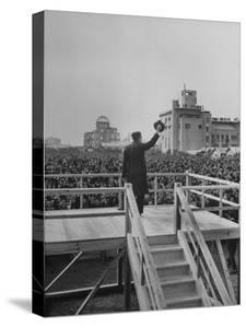Emperor Hirohito Standing on Platform and Waving to the Crowd by Carl Mydans