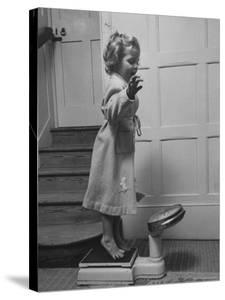 Grand Daughter of Winston Churchill, Arabella Spencer Churchill, Jouncing on Bathroom Scale by Carl Mydans
