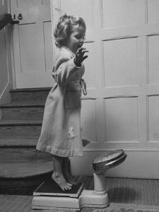 Grand Daughter of Winston Churchill, Arabella Spencer Churchill, Jouncing on Bathroom Scale by Carl Mydans