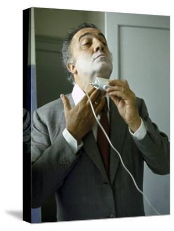 Director Federico Fellini with Powder on His Face as He Shaves with an Electric Shaver