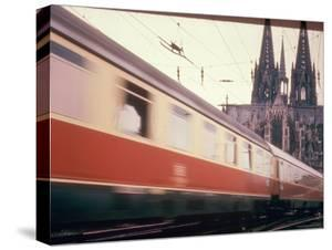 Eurailpass in Europe: Germany's Parsifal Express Speeding Past Cologne Cathedral by Carlo Bavagnoli
