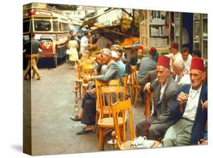 Lebanese Gentlemen sits at a steetside cafe sipping tea and smoking traditional narghile pipes by Carlo Bavagnoli