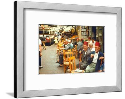 Lebanese Gentlemen sits at a steetside cafe sipping tea and smoking traditional narghile pipes