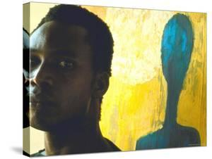 Portrait of Nigerian Artist Erhabor Emokpae Standing Next to One of His Colorful Paintings by Carlo Bavagnoli