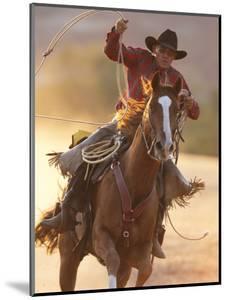 Cowboy Galloping While Swinging a Rope Lassoo at Sunset, Flitner Ranch, Shell, Wyoming, USA by Carol Walker