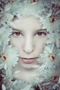 Close Up of Young Girls Face in Flowers by Carolina Hernandez