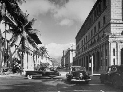 Cars Crossing an Intersection on a Downtown Honolulu Street with Mountains in the Background