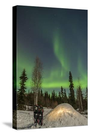 USA, Alaska, Fairbanks. a Quinzee Snow Shelter and Aurora Borealis