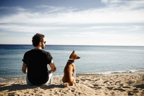 Caucasian Man in Sunglasses Sitting in Beach with Friend's Dog Breed Basenji and Looking into the D-avemario-Photographic Print