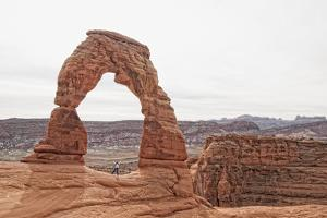 A Tourist Poses Beneath a Natural Arch in Arches National Park by Cesare Naldi