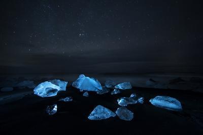 Glacier Ice Illuminated on Black Sand Beach in Jokulsarlon, Iceland