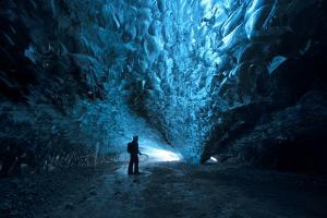Silhouette of a Person Exploring an Ice Cave in Vatnajokull National Park, Iceland by Chad Copeland