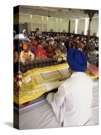 Sikh Priest and Holy Book at Sikh Wedding, London, England, United Kingdom