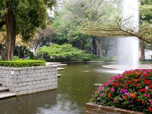 Pond With Fountain in Kowloon Park, Tsim Sha Tsui Area, Kowloon, Hong Kong, China by Charles Crust