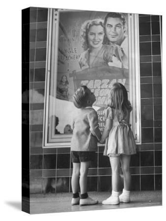 Children Looking at Posters Outside Movie Theater