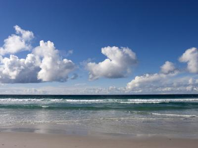 Gentle Waves and Surf Surging onto a Flat Beach under Puffy Clouds by Charles Kogod