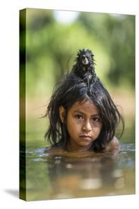 A Pet Saddleback Tamarin Hangs on Tight to a Matsigenka Girl as She Swims in the Yomibato River by Charlie Hamilton James