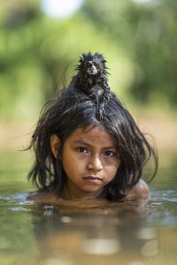 A Pet Saddleback Tamarin Hangs on Tight to a Matsigenka Girl as She Swims in the Yomibato River by Charlie Hamilton James