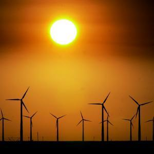 A Group of Wind Turbines are Silhouetted by the Setting Sun by Charlie Riedel