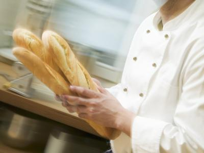 Chef Hurrying Through Kitchen with Baguettes--Photographic Print