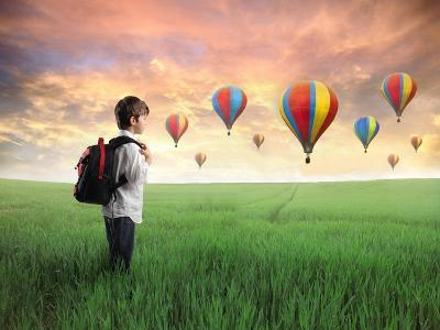 Child Carrying A Backpack Standing On A Green Meadow With Hot-Air Balloons In The Background-olly2-Art Print