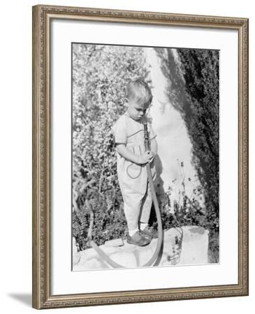 Child Pointing Hose at Face--Framed Photo