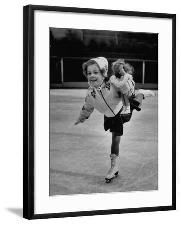 Child Skater Helen Ann Rousselle Holding Doll While Skating across the Ice--Framed Photographic Print