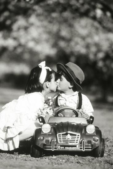 Children Kiss in Toy Car--Photographic Print