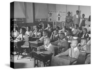 Children Sitting at their Desks in a Classroom, Teachers at the Rear of the Room