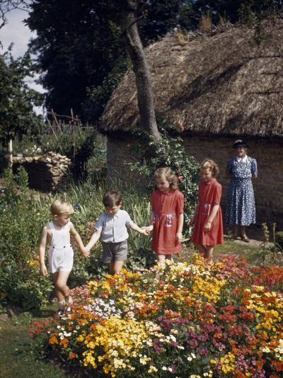 Children Walk in a Flower Garden as a Smiling Older Woman Watches-Melville Grosvenor-Photographic Print