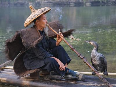 China, Guangxi Province, Yangshuo, Fisherman Smoking a Pipe on the Bamboo Raft on the Li River-Keren Su-Photographic Print