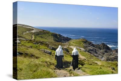 Two Nuns Walking on a Beach in Ireland