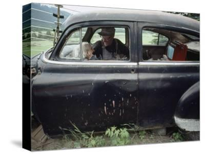 A Mother and Son Watch Television in an Old Car