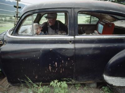 A Mother and Son Watch Television in an Old Car by Chris Johns