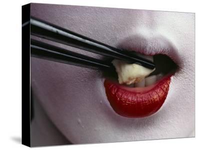 Close View of a Geisha Eating Tofu with Chopsticks