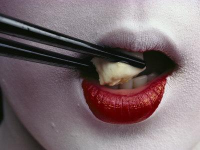 Close View of a Geisha Eating Tofu with Chopsticks