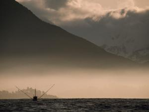 Fishing Boat Working in Moring Fog Off of a Mountainous Coast by Chris Johns