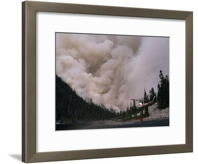 Helicopter Carrying Water from a River to Fight a Forest Fire