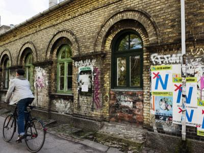 Cyclist in Freetown Christiania, with Anti European Union Posters on Wall